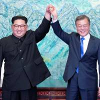 South Korean President Moon Jae-in and North Korean leader Kim Jong Un raise their hands at the truce village of Panmunjom inside the Demilitarized Zone, which separates the two Koreas, on Friday. | KOREA SUMMIT PRESS POOL / VIA REUTERS