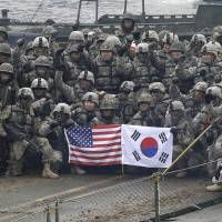 U.S. and South Korean soldiers pose on a floating bridge on the Hantan River during a joint military exercise against a possible attack from North Korea, in Yeoncheon, South Korea, in December 2015. | AP