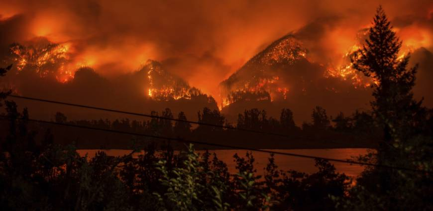 A wildfire is seen from near Stevenson, Washington, across the Columbia River, burning in the Columbia River Gorge above Cascade Locks, Oregon, last September. A teenager who started the major wildfire in the scenic Columbia River Gorge in Oregon has been ordered to pay restitution for at least the next decade, though it's unlikely the boy will ever cover his nearly $37 million bill. | TRISTAN FORTSCH / KATU-TV / VIA AP