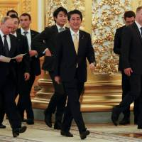Russian President Vladimir Putin and Prime Minister Shinzo Abe enter a hall before a communication session with the crew of the International Space Station at the Kremlin in Moscow on Saturday. | REUTERS