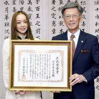 Pop singer Namie Amuro receives a certificate honoring her achievements from Okinawa Gov. Takeshi Onaga at a ceremony at the Okinawa Prefectural Government office in Naha on Wednesday. | KYODO