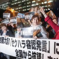 Women protest against Finance Minister Taro Aso during a rally outside his ministry on Monday evening. | KYODO