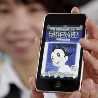 A woman in Beijing shows a mobile phone displaying an image of 'Astro Boy,' a manga character created by Japan's Osamu Tezuka, on April 7, 2010. | KYODO
