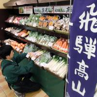 A sales clerk at a supermarket in Tokyo's Suginami Ward stacks shelves with vegetables delivered by highway express bus from Takayama, Gifu Prefecture. | CHUNICHI SHIMBUN