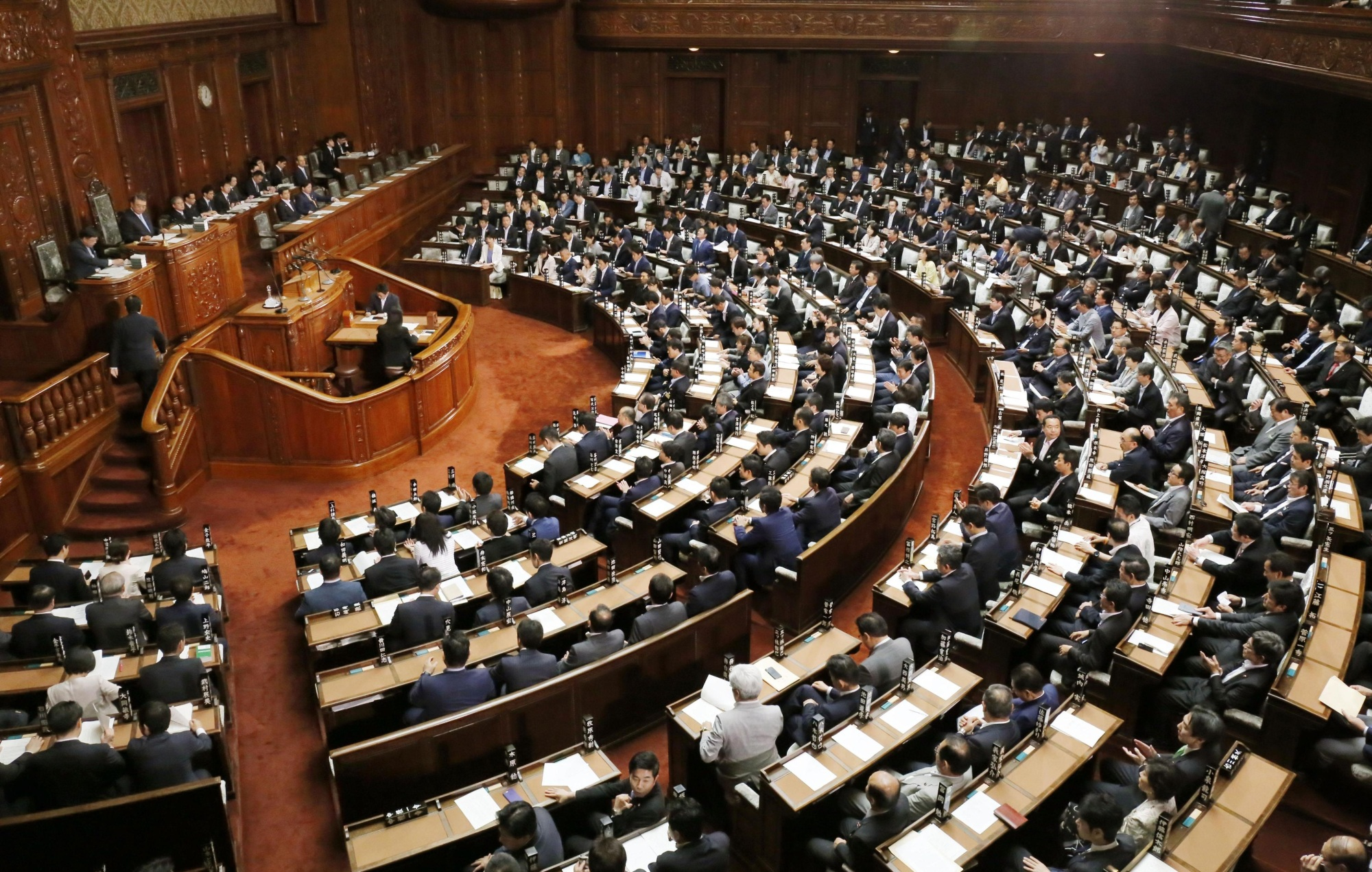Lawmakers attend a plenary session at the Lower House on Tuesday afternoon. Ruling bloc sources said the government and its coalition partners are now considering extending the current ordinary Diet session to the end of June or early July to secure the passage of bills on labor reform and casinos. | KYODO