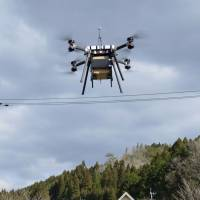 A drone carries a 10-kg parcel during a trial run in Saiki, Oita Prefecture, on March 9. | KYODO