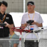 A student practices flying a drone at a school in Tokyo's Koto Ward on May 15. | YOSHIAKI MIURA