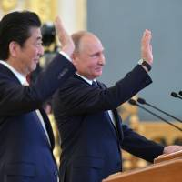 During their meeting in the Kremlin in Moscow on Saturday, Prime Minister Shinzo Abe and Russian President Vladimir Putin wave while talking to  astronauts aboard the International Space Station. | AP