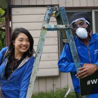 Sayaka Watanabe (right) cleans up a 'share house' with an asylum-seeker from Angola in Oami, Chiba Prefecture, on April 14. | CHISATO TANAKA