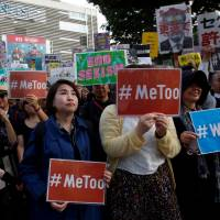 Protesters hold placards during a rally against harassment at Shinjuku shopping and amusement district in Tokyo on April 28. | REUTERS