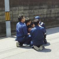 Tatsuma Hirao (center), who had been on the run after escaping from a prison in Ehime Prefecture in April, is captured by police officers in the city of Hiroshima on Monday in this photo taken by a local resident. | KYODO