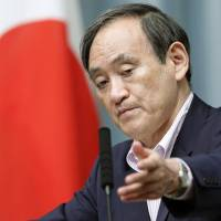 Chief Cabinet Secretary Yoshihide Suga takes questions at a news conference Friday. | KYODO