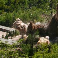 Smoke and debris rise into the air as barracks buildings for guards and tunneling workers, at North Korea's nuclear test site at its Punggye-ri facility in North Hamgyong province, are blown up on Thursday. | AP