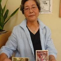 In an interview in May in Osaka, Chon Hi Sun holds a photo of her parents (left), who were born in what is now North Korea, along with her husband and younger daughter, and a photo of her taken nearly a half century ago with a group of Korean residents. | ERIC JOHNSTON