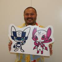Tokyo 2020 Olympic and Paralympic mascot designer Ryo Taniguchi holds up his winning designs, on April 26 in Tokyo. | KYODO