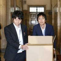 Finance Ministry officials bring boxes containing documents on the shady land deal involving school operator Moritomo Gakuen into the Diet building Wednesday. | KYODO