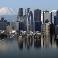 Mount Fuji and Tokyo buildings are reflected on a table. A government report says if Mount Fuji were to erupt, it could rain volcanic ash on Tokyo and paralyze the capital. | BLOOMBERG