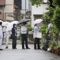 Investigators enter the home of inmate Kunihiko Katsuta in Kakogawa, Hyogo Prefecture, Wednesday after he confessed to involvement in the murder of a 9-year-old girl in 2004. | KYODO