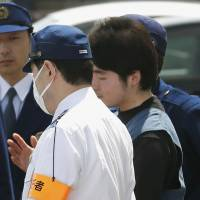 Haruka Kobayashi is taken by police to be turned over to prosecutors in the city of Niigata on Tuesday. | KYODO