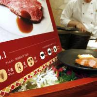 A sign explaining the use of dietary pictograms is placed beside a dish at a restaurant in Osaka in April. | KYODO