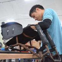 Hiroki Nakajima repairs a wheelchair at a service center during the Winter Paralympics in Pyeongchang, South Korea, on March 15. He was one of two Japanese technicians at the facility run by German company Ottobock. | KYODO