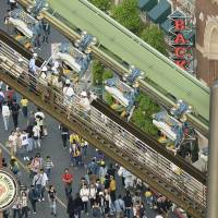 Passengers are rescued from a roller coaster at Universal Studios Japan in Osaka on Tuesday. The ride stopped when a safety device detected an abnormality, leaving some riders suspended in a prone position for two hours. | KYODO