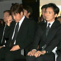 Pop stars Goro Noguchi (left) and Hiromi Go, both 62, attend the funeral of fellow singer Hideki Saijo on Saturday in Tokyo. The trio were dubbed the Shin Gosanke (New Big Three) male pop stars of their generation during their glory days. Saijo died at the age of 63 on May 16. | KYODO