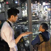 American tourist Emi Estrada listens to guide Shogo Nomura during a nighttime tour last month of the Shibuya district in Tokyo. | KYODO