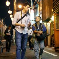 Tourist Emi Estrada of the United States strolls past a bar in Tokyo's Shibuya district in April, guided by Shogo Nomura during a night tour organized by the local tourism association. | KYODO