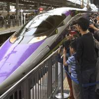 Fans snap photos of a lavender,  anime-themed shinkansen based on 'Shinseiki Evangelion' ('Neon Genesis Evangelion') on Sunday, the last day of its extended run, at JR Shin-Osaka Station. The bullet train, which debuted in 2015 between Shin-Osaka and Hakata stations, was supposed to be taken out of service in March 2017 but was extended by popular demand.  | KYODO