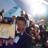 Director Hirokazu Kore-eda poses with his trophy on Saturday during a photocall after he won the Palme d'Or for the film 'Shoplifters' '(Manbiki Kazoku)' at the 71st edition of the Cannes Film Festival in Cannes, southern France. | AFP-JIJI