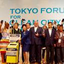 Joined by governors and mayors from global megacities, Tokyo Gov. Yuriko Koike (center) prepares to drop a used cell phone into a recycling collection box during a two-day symposium that concluded on Wednesday in Tokyo.