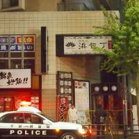 Police officers stand guard outside an izakaya restaurant where a knife-yielding man stabbed four family members in the city of Chiba on Sunday. | KYODO