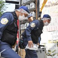 Investigators enter a Japanese pub Monday where a family of four was stabbed by a knife-wielding relative the previous night in the city of Chiba. | KYODO