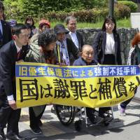 Kikuo Kojima (seated in a wheelchair) heads to Sapporo District Court in Sapporo on Thursday. | KYODO