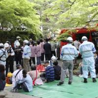 Firefighters look after people who evacuated from Nanzenji temple in Kyoto, where a pungent chemical smell forced about 70 visitors to evacuate Wednesday. | KYODO