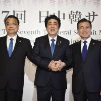 Chinese Premier Li Keqiang (from left to right), Prime Minister Shinzo Abe and South Korean President Moon Jae-in pose for photographers prior to their summit in Tokyo on Wednesday. | KYODO