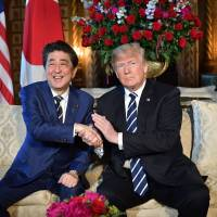 U.S. President Donald Trump greets Japanese Prime Minister Shinzo Abe at Trump's Mar-a-Lago resort in Palm Beach, Florida, April 17. Trump and Abe agreed on Monday that it is 'imperative' to completely dismantle North Korea's nuclear weapons and ballistic missile program, the White House said. The U.S. and Japanese leaders will meet ahead of a much anticipated summit with North Korea's Kim Jong Un back on schedule for June 12 in Singapore just days after Trump announced he was canceling it. | AFP-JIJI