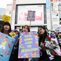 Demonstrators hold signs during a rally against sexual harassment in Shinjuku Ward, Tokyo, on April 28. | BLOOMBERG