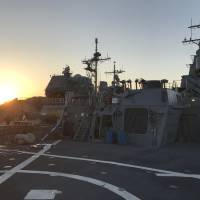 The setting sun is seen behind the helicopter landing deck of the USS Milius guided-missile destroyer after it arrived Tuesday at the U.S. Navy's Yokosuka base in Kanagawa Prefecture. | JESSE JOHNSON