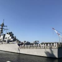 Crew members of the USS Milius guided-missile destroyer stand at attention as it arrives Tuesday at the U.S. Navy's Yokosuka base in Kanagawa Prefecture. | JESSE JOHNSON
