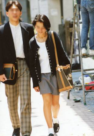 A couple wearing the coordinated fashion style known as shibu-kaji (Shibuya casual) walk down a street in Tokyo in the early 1990s.