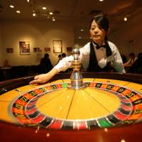 A woman spins a roulette wheel at a mock casino operated by Japan Casino School in Tokyo. | BLOOMBERG