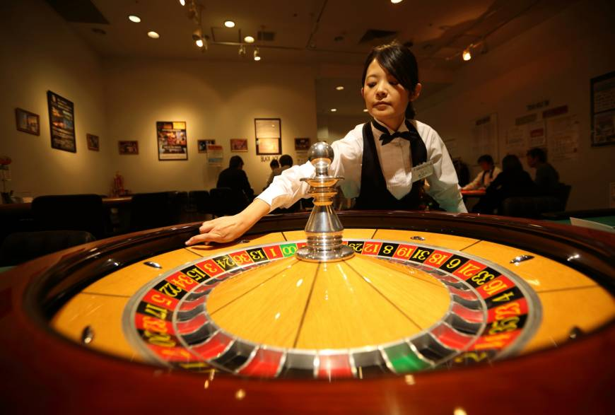 A woman spins a roulette wheel at a mock casino operated by Japan Casino School in Tokyo.