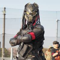 A man takes part in an airsoft game at Tokyo Sabage Park in China Prefecture wearing body armor and a mask of the alien warrior character from the movie 'Predator.' | MARK THOMPSON