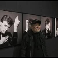Iconic image: Masayoshi Sukita stands in front of the picture he took of David Bowie in 1977. The shot was used as the cover art for Bowie's 'Heroes' album. | © 2018 'SUKITA' PARTNERS