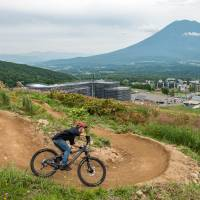 Forget your skis: A mountain biker navigates a trail with Mount Yotei in the background.   GLEN CLAYDON