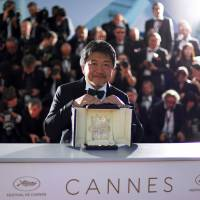 Master class: Director Hirokazu Kore-eda poses with his Palme d'Or trophy at the Cannes Film Festival on May 19. He won the event's top prize for his film, 'Shoplifters.' | AFP-JIJI