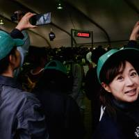 ¥20 million and climbing: Azusa Urata, the 2017 festival's only female competor, reacts to the growing bid for a cow. | LANCE HENDERSTEIN