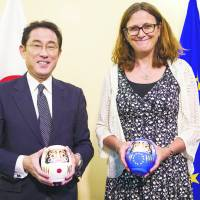 Then-Foreign Minister Fumio Kishida (left) and European Commissioner for Trade Cecilia Malmstroem pose with daruma dolls after reaching a consensus on a bilateral economic partnership agreement in Brussels on July 5. | EUROPEAN UNIONE